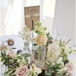 A Rustic Centerpiece, With Wood Slices, Various Arrangements, Candles And A Table Number | Undbraut.com