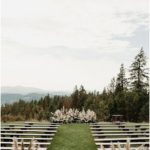 Outdoor wedding ceremony with white benches overlooking beautiful mountain landscapes ...